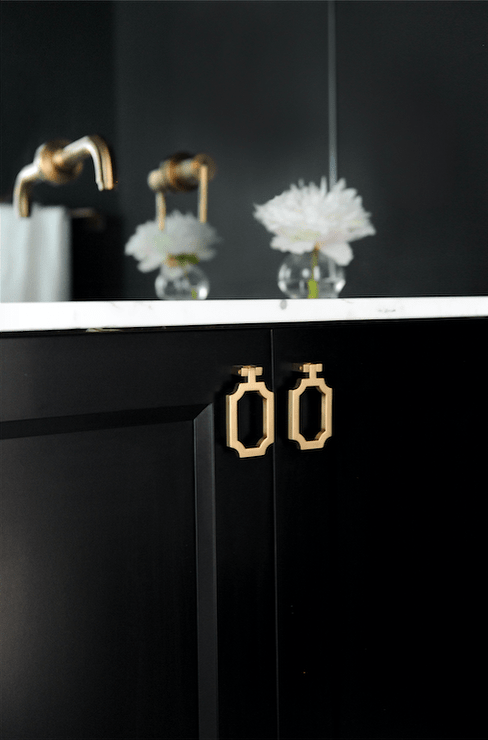 Black washstand fitted with gold pulls and white marble countertop. Design by Chrissy and Co