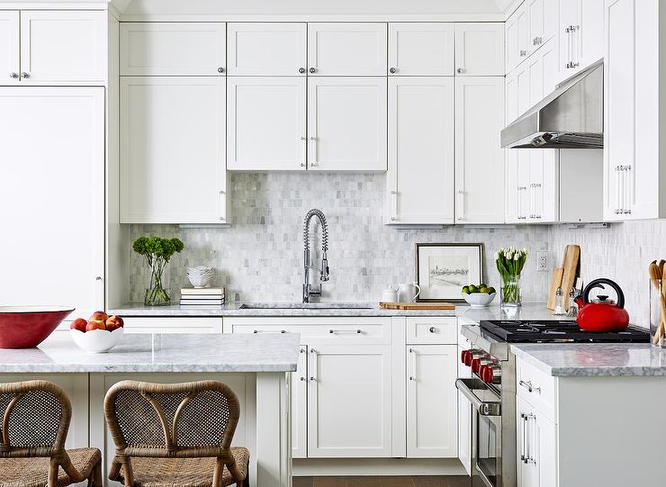 Stacked white shaker cabinets offer plenty of storage space. Design by Breeze Giannasio